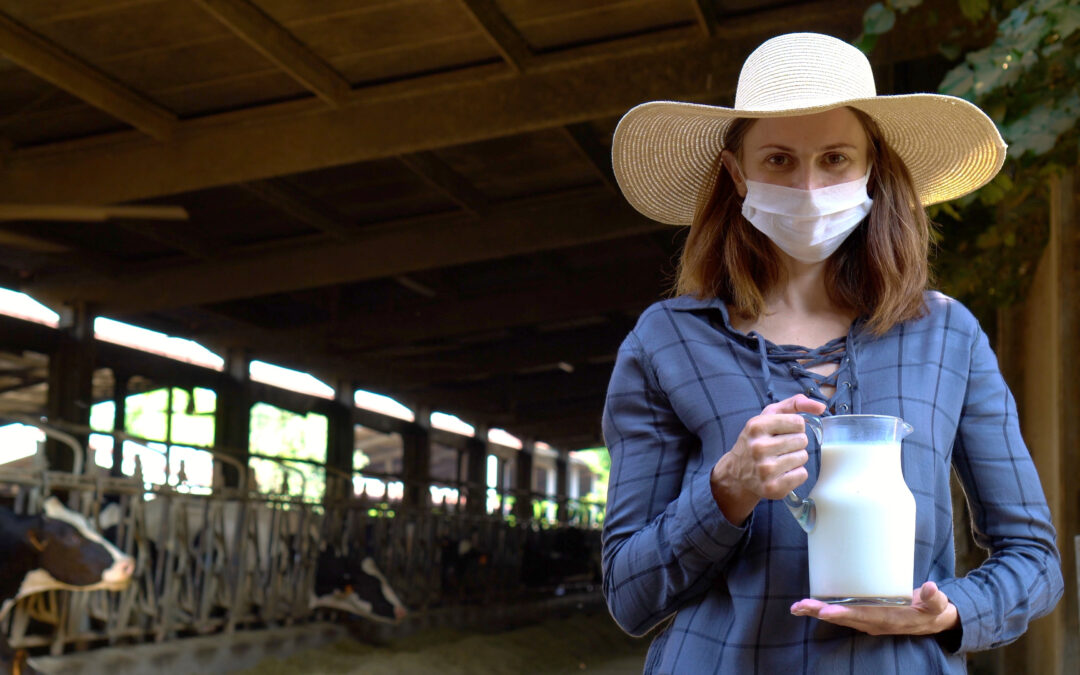 dairy farmer wearing mask holds milk jug